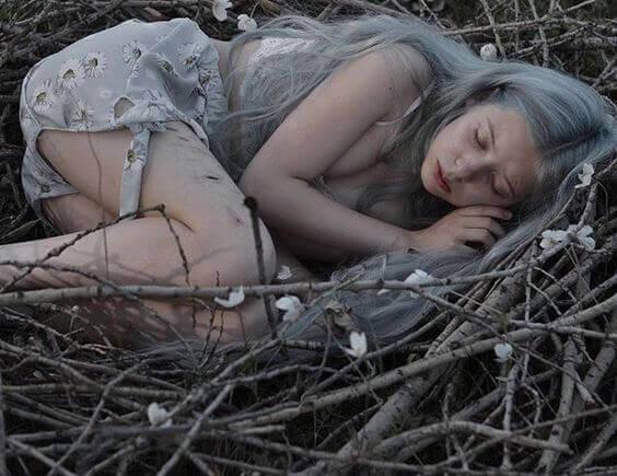 Kvinna som ligger bland kvistar.