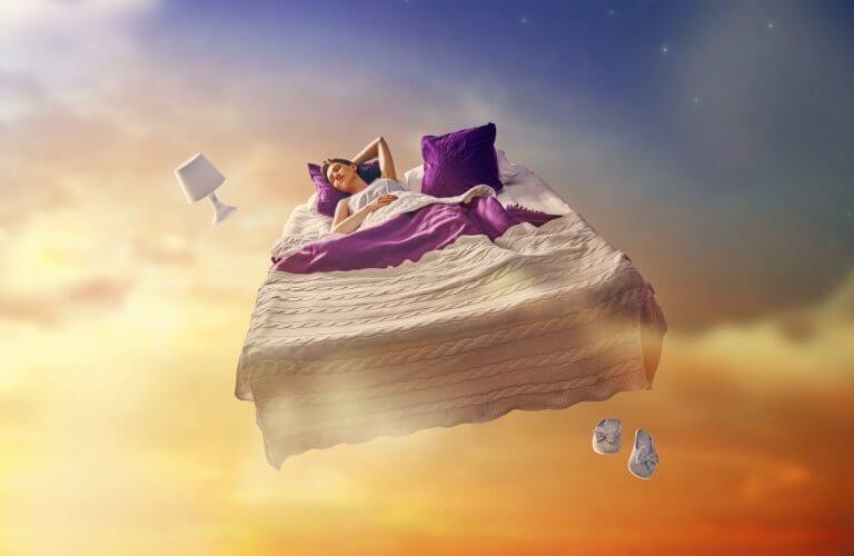 Kvinna som sover på säng bland molnen.