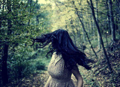 Kvinna som springer i skogen.