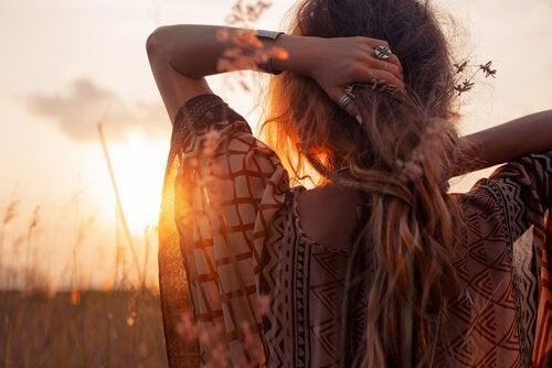 Fri kvinna tittar på solnedgång