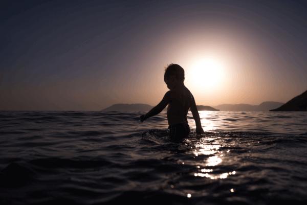 En liten pojke som badar i havet