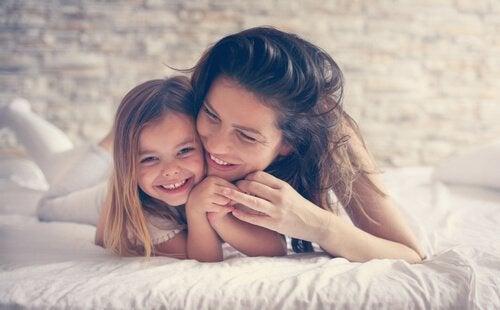 Mor med sin dotter i sängen