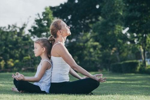 mor och dotter mediterar utomhus