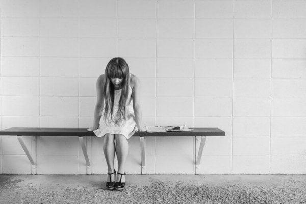 Orolig kvinna sitter på en bänk