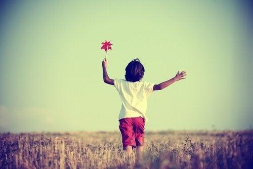 Pojke med vindsnurra leker självständigt på fält