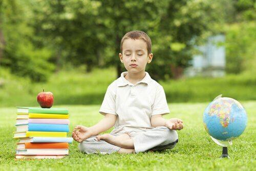pojke mediterar i gräset med skolböcker bredvid