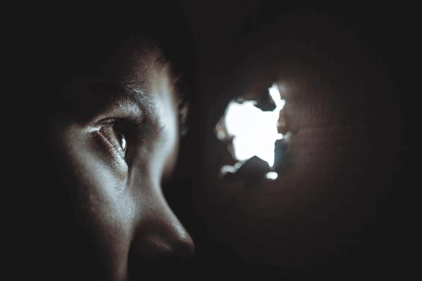 En pojke som upplever separationsångest tittar ut genom ett hål i en låda