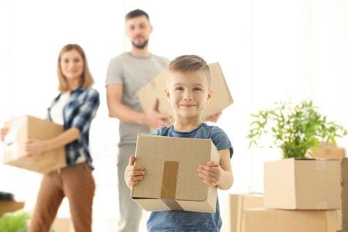 Son som hjälper sina föräldrar att packa upp flyttlådor