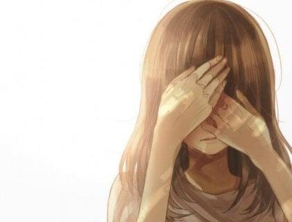 Flicka som täcker ansiktet med händerna