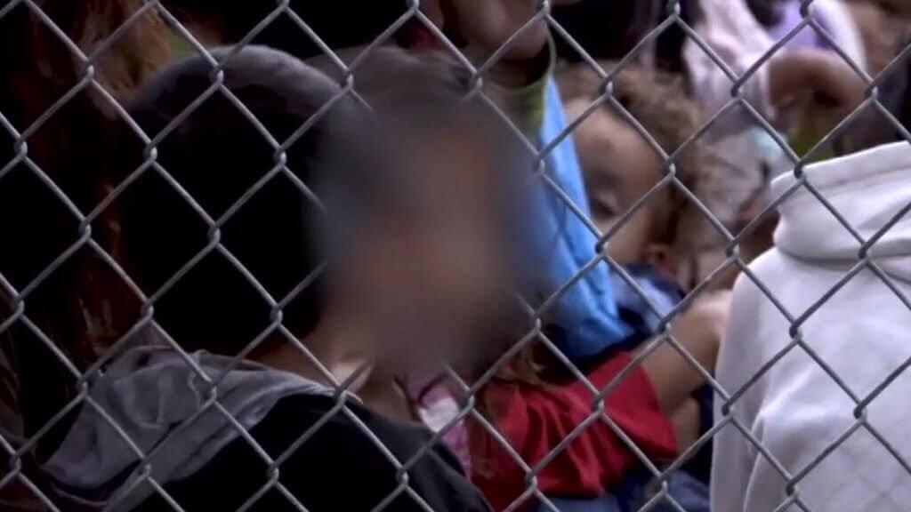 Barn bakom stängsel.