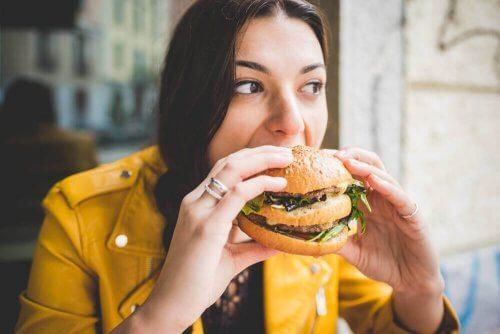 Kvinna som äter hamburgare.