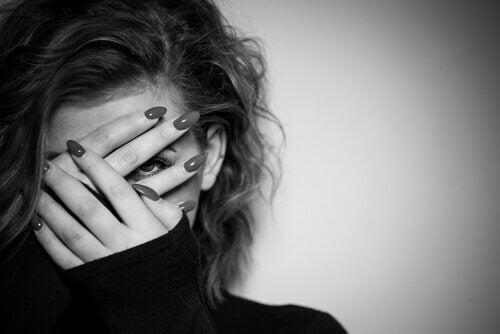 Kvinna som håller händerna framför ansiktet.