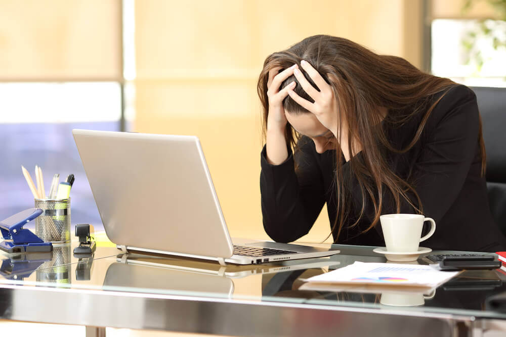 Kvinna som ser trött ut framför sin laptop.