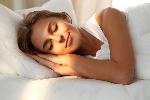 Kvinna som sover i sängen.