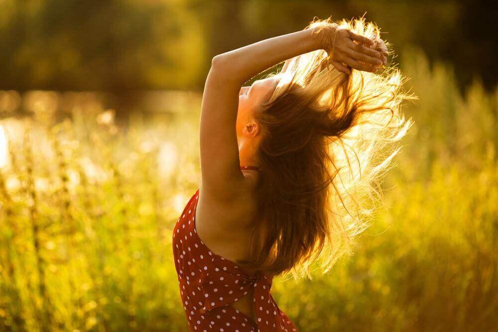 Kvinna som står i ett fält och är glad.