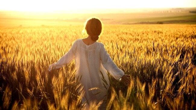 Kvinna som står i ett fält.