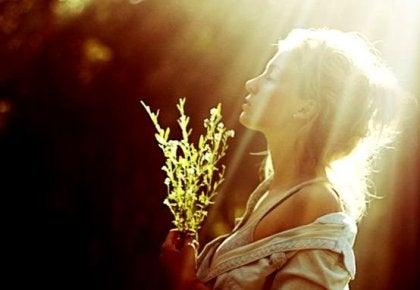 Kvinna som står i solskenet.