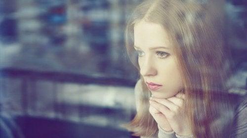 Kvinna som tittar dyster genom ett fönster.