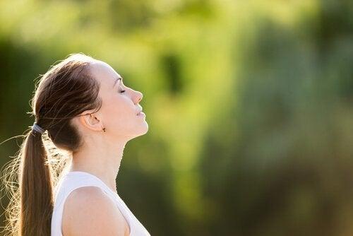 Kvinna som utför andningsövningar.