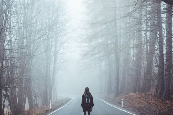 Ensam kvinna på en väg i skogen