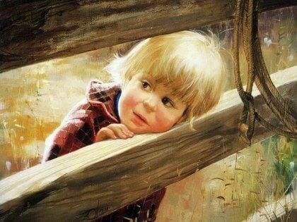 Liten pojke tittar ut från staket