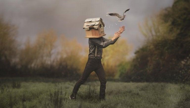 Man med fågelhus på huvudet