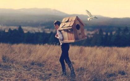 Man med fågelhus på ryggen.