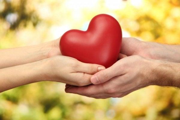Man och kvinna som håller ett hjärta.