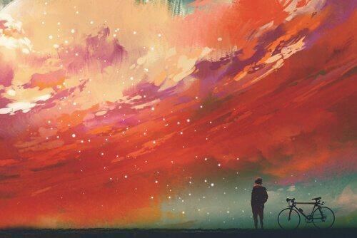 Man som står bredvid sin cykel.