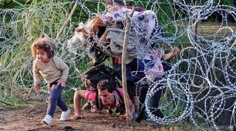 Människor kryper under taggtråd