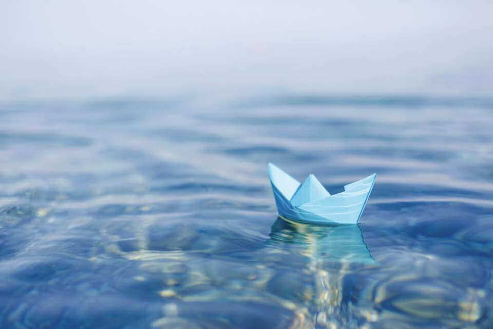 Pappersbåt i vattnet.