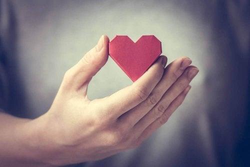 Person som håller i ett hjärta.