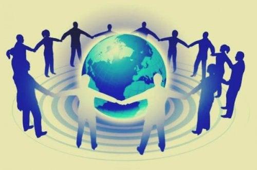 Personer som håller hand runt en jordglob.