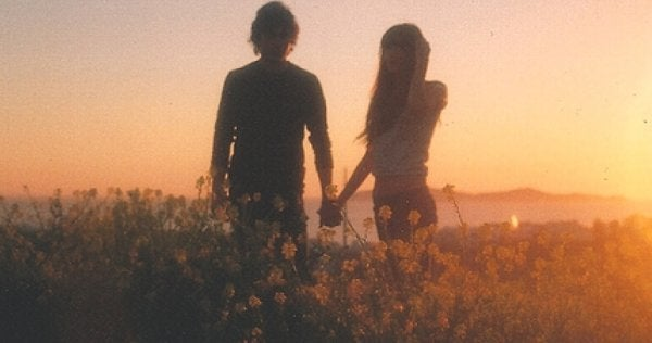 Ungt par håller handen i fält