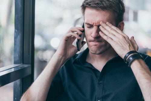 En man med mobiltelefon mot örat och sammanpressade läppar verkar vara arg