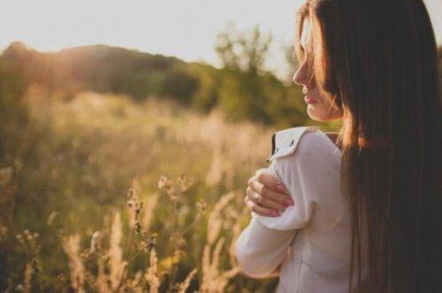 Kvinna i profil ute i soligt naturområde håller sig om axeln