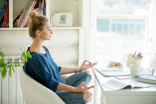 Kvinna mediterar innomhus vid skrivbord