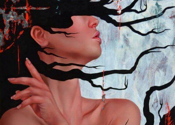 Kvinna som är täckt av svarta grenar.