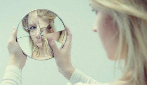 En kvinna tittar på sig själv i en trasig spegel