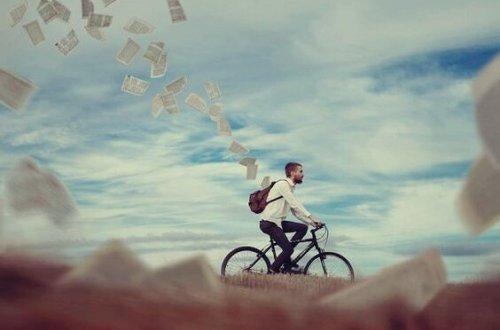 Man cyklar med massor av pappersark som fladdrar ut ur hans ryggsäck