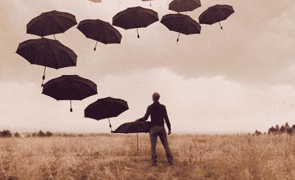 Man på ett fält med massor av paraplyn i luften