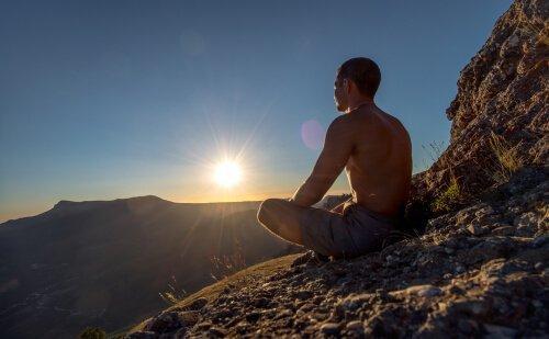 Man mediterar på ett berg