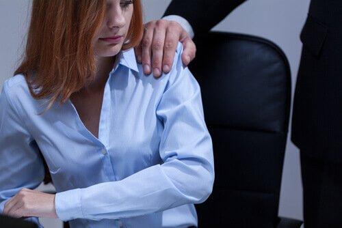 En kvinna på ett kontor med en mans hand på axeln
