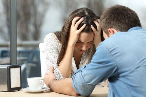 Man håller tag om kvinna med huvudbry vid fikabord