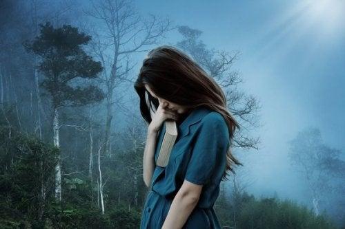 Ensam kvinna i skogen med bok i handen