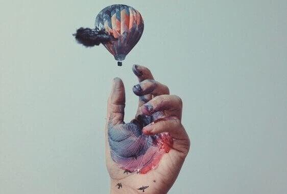 Hand med vattenfärg och liten luftballong