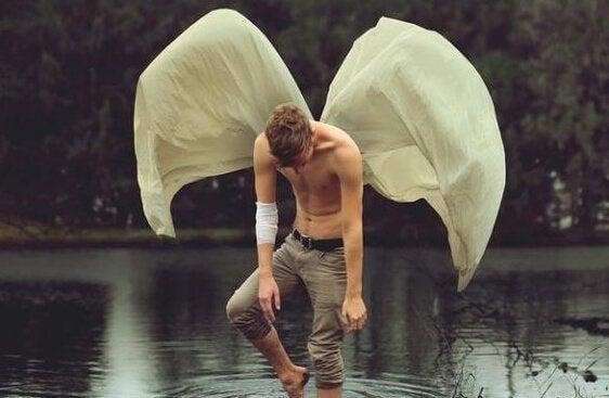 Man med vingar badar i sjö