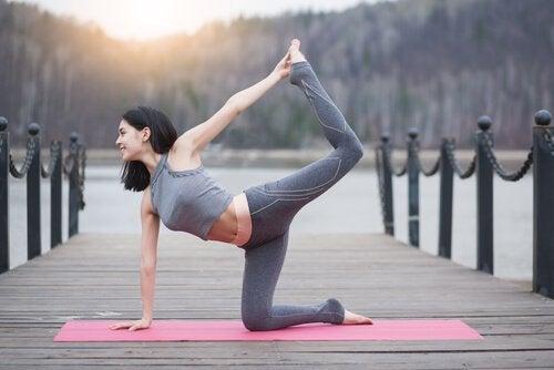 Kvinna gör yoga på brygga
