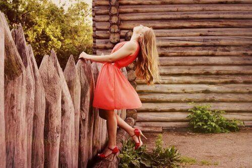 Kvinna med röd klänning vid stuga.
