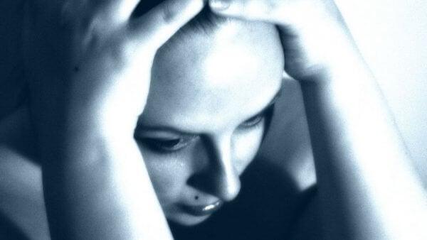 Kvinna håller händer på huvud